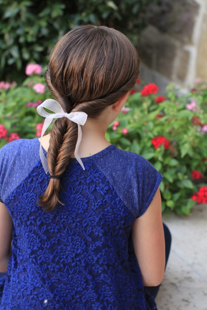 "Back view of young girl standing outside and modeling ""Double-twist"" ponytail"
