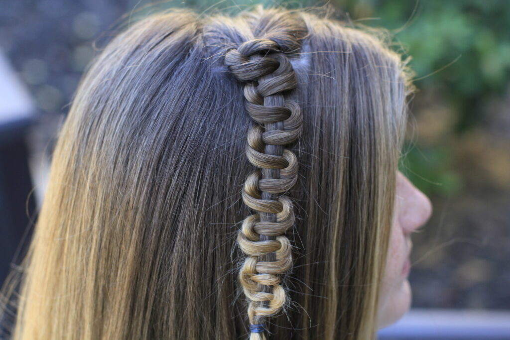 "Side view of young girl modeling ""Teen Slide-Up Braid"" hairstyle outside"