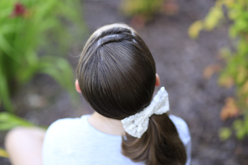 """Back view of young girl outside modeling """"Knots into Side Ponytail"""" hairstyle"""