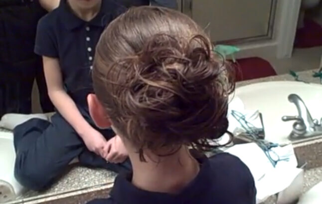 """Back view of young girl modeling """"Messy Bun"""" hairstyle"""