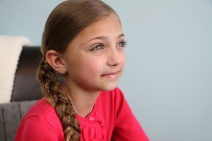 Portrait view of a young girl modeling the Micro-Braid Accented Side Braid | Braided Hairstyles