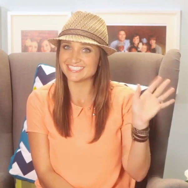 Woman wearing a hat and orange shirt sitting the living room waving hello