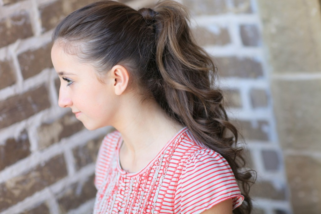 """Young girl outside modeling a red shirt modeling the """"perfect ponytail"""""""