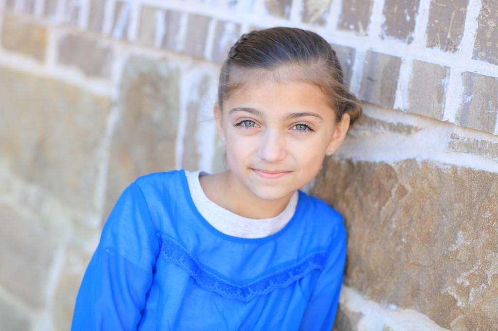 Portrait of a little girl outside in a blue shirt modeling Zipper Braid | Updo Hairstyles