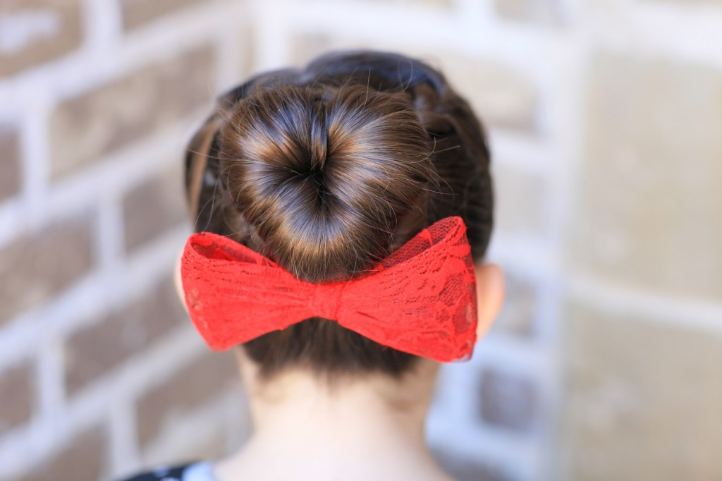 "Young girl outside modeling ""Love Bun"" with a red bow in her hair 