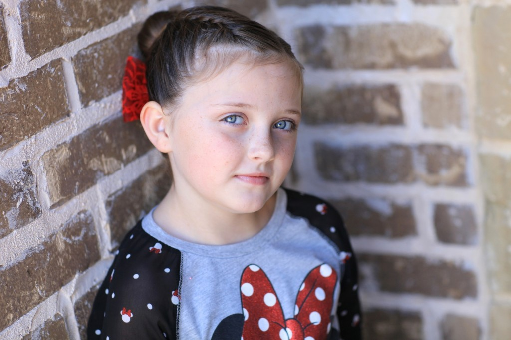 "Portrait of young girl outside modeling ""Love Bun"" with a red bow in her hair 