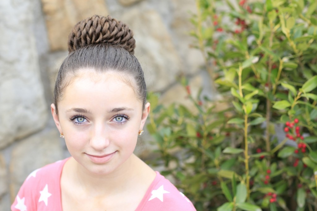 Young girl standing outside modeling Rope Twisted Pinwheel Bun | Prom Hairstyles