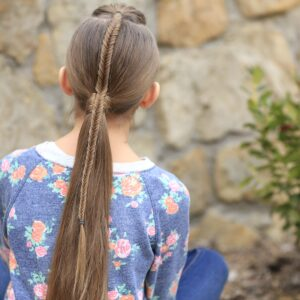 Young girl standing outside modeling Fishtail-Accented Ponytail | Hairstyles for Sports