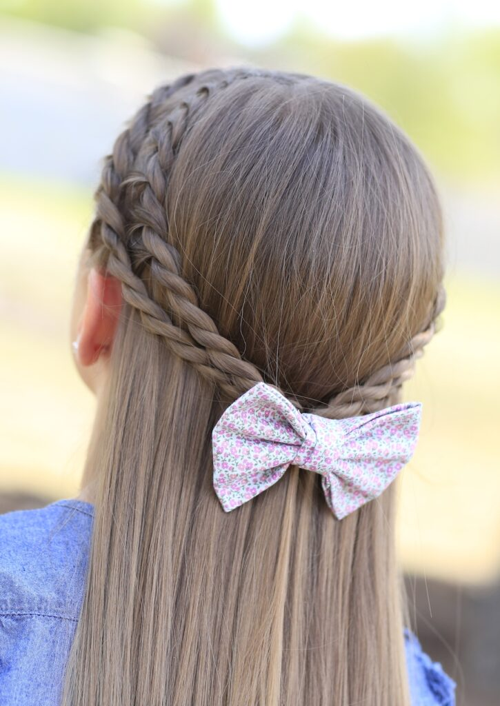 Young girl outside modeling Rope Braid Tieback Hairstyle