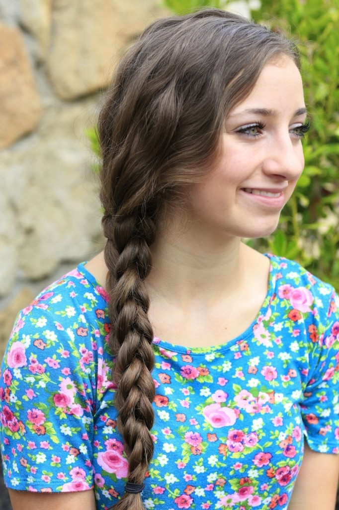 Young girl outside wearing a floral blue shirt modeling 3D Split Braid