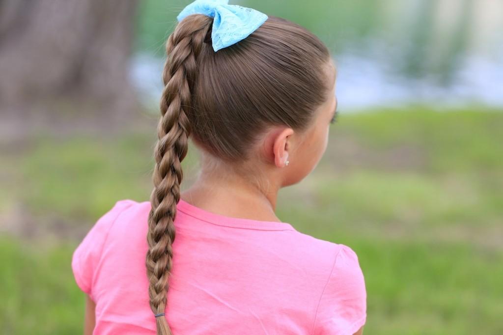 Little girl outside wearing a pink shirt modeling 3D Split Braid