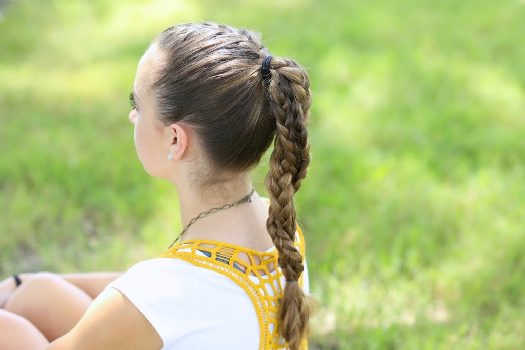 Young girl standing outside modeling The Run Braid Combo | Hairstyles for Sports