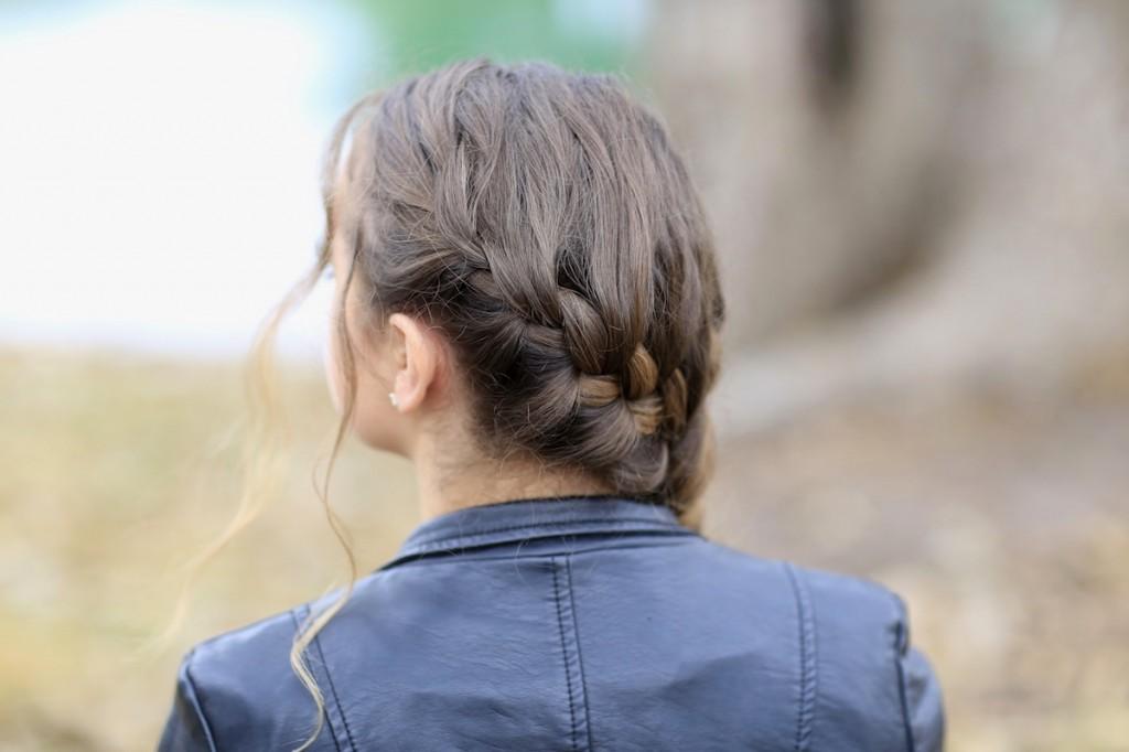 Girl outside wearing a back jacket modeling Katniss' Mockingjay Braid | Hunger Games Hairstyles (Back)