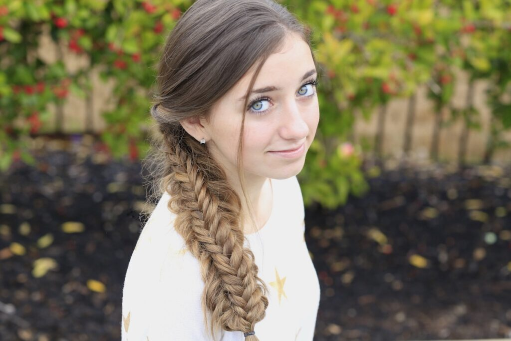 Young girl outside wearing a white shirt modeling Messy Split Fishtail Braid