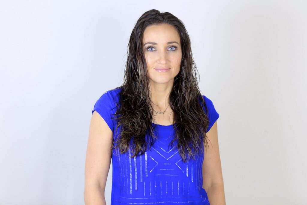 Portrait of woman with the blue shirt standing in front of a white background