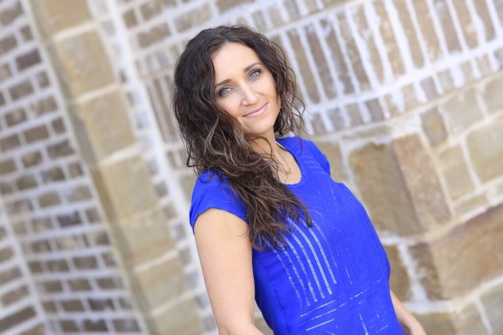 Woman with curly hair wearing a blue shirt outside in front of a brick background