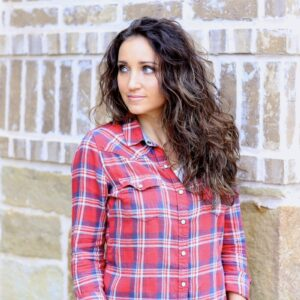 Woman with curly hair wearing a red plaid shirt standing outside in front of a brick background