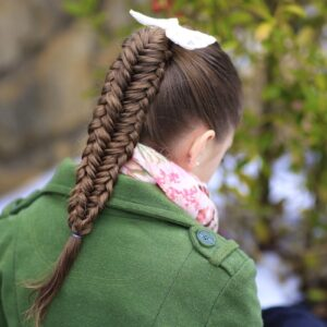 Young girl outside in a winter coat modeling Twisted Edge Fishtail Combo   Braid and Updo
