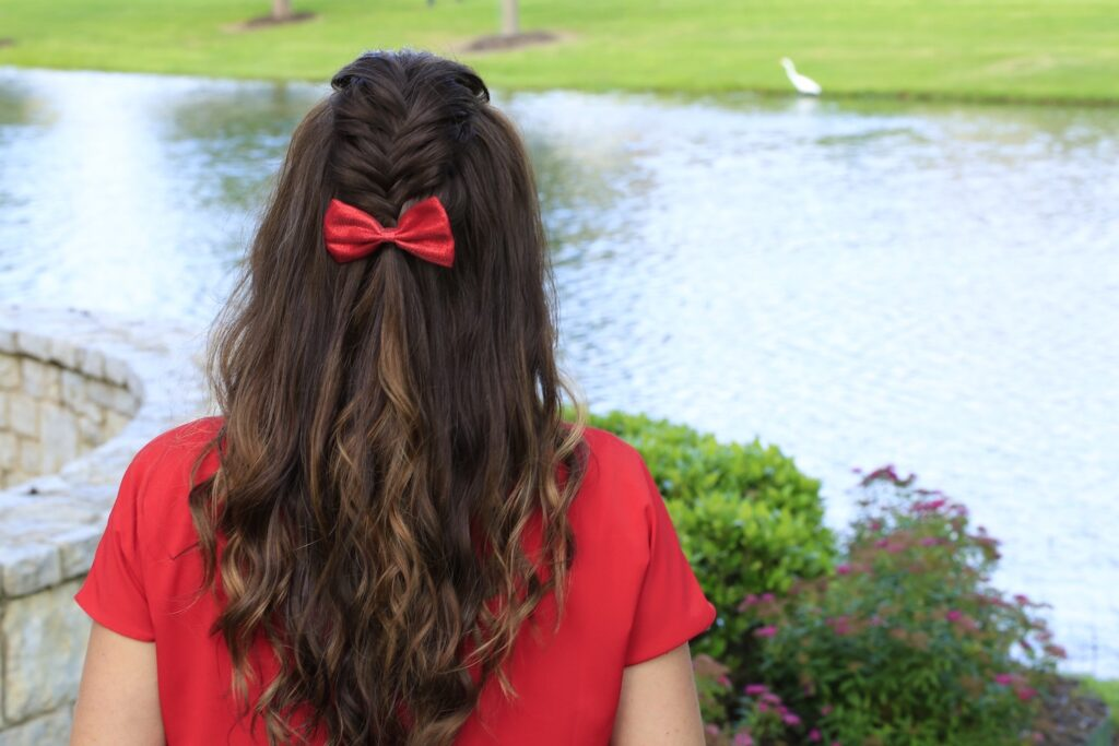 "Back view woman wearing a red shirt and red bow in her hair standing by the lake modeling ""Woven Faux Hawk"" hairstyle"