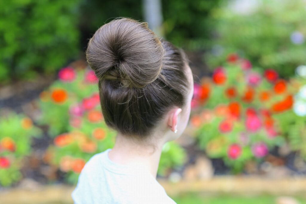 Portrait of a young girl modeling The Fan Bun | Prom Updos (Back)