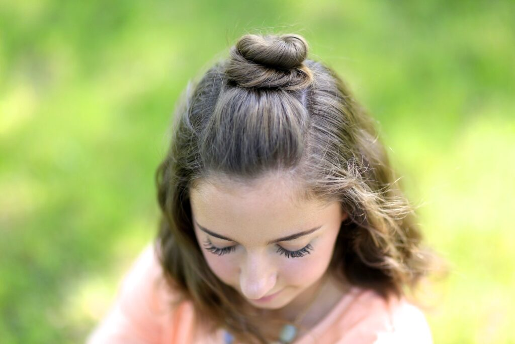 Young girl standing outside modeling Half Up Bun