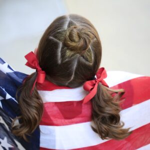 Little girl holding American flag modeling Star Bun Combo | 4th of July Hairstyles
