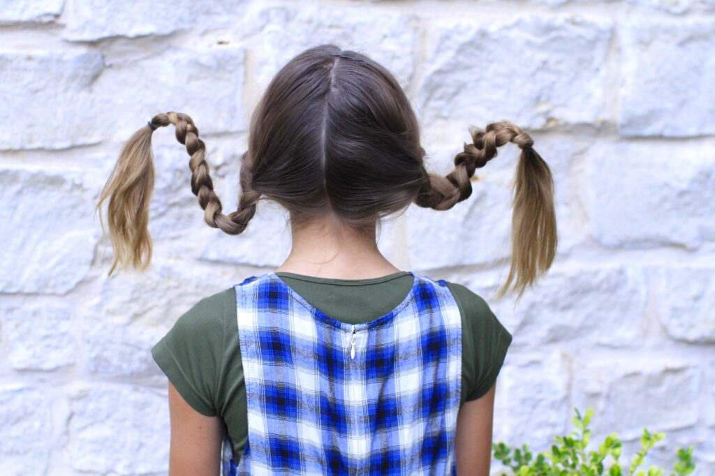 Young girl outside modeling Pippi Longstock Braids | Easy Halloween Hairstyles (Back)