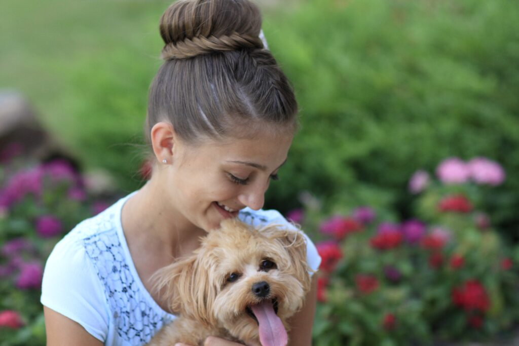 Young girl outside holding a puppy and modeling Lace Fishtail Bun