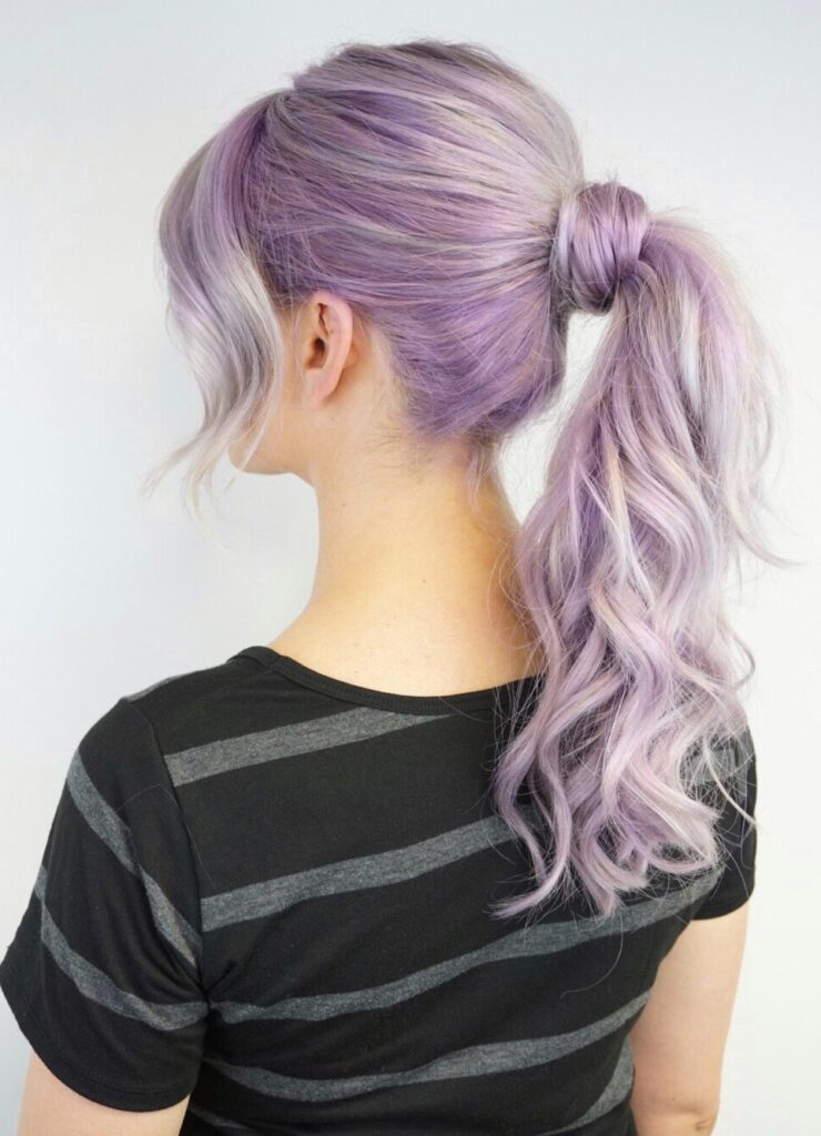 Side view of girl with lavender modeling a high ponytail in front of a white background
