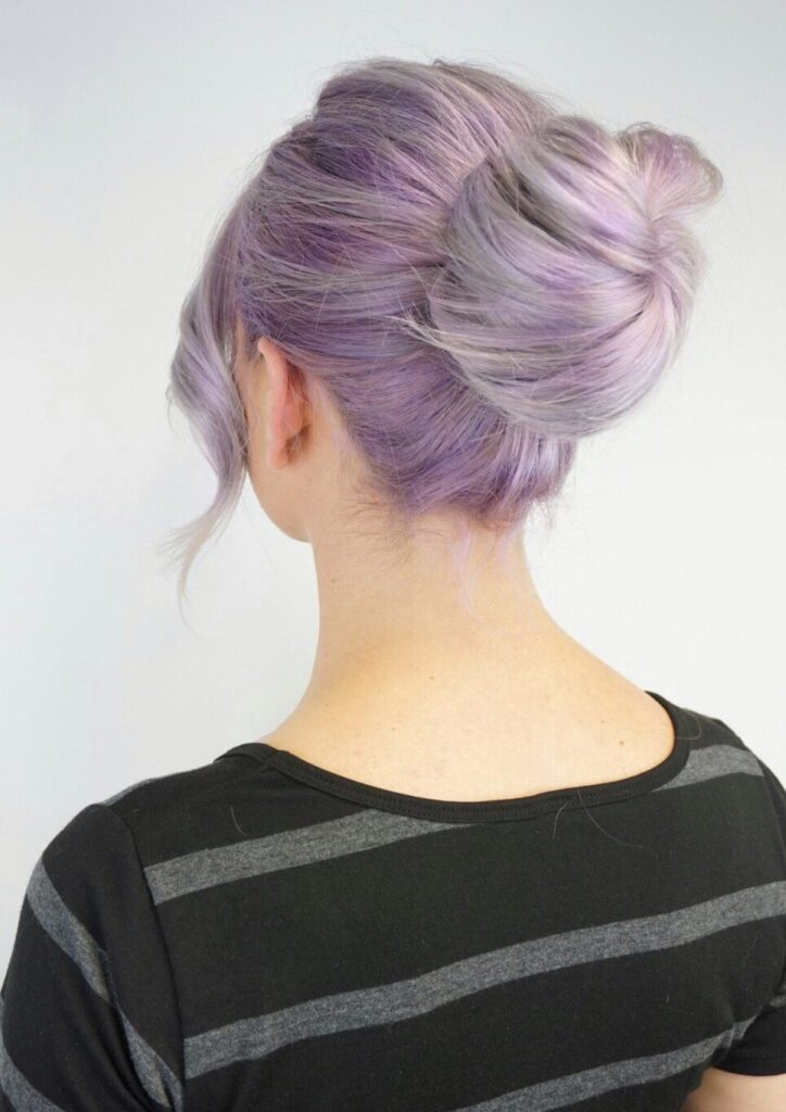 "Back view of girl with lavender modeling her hair in a ""bun"" in front of a white background"