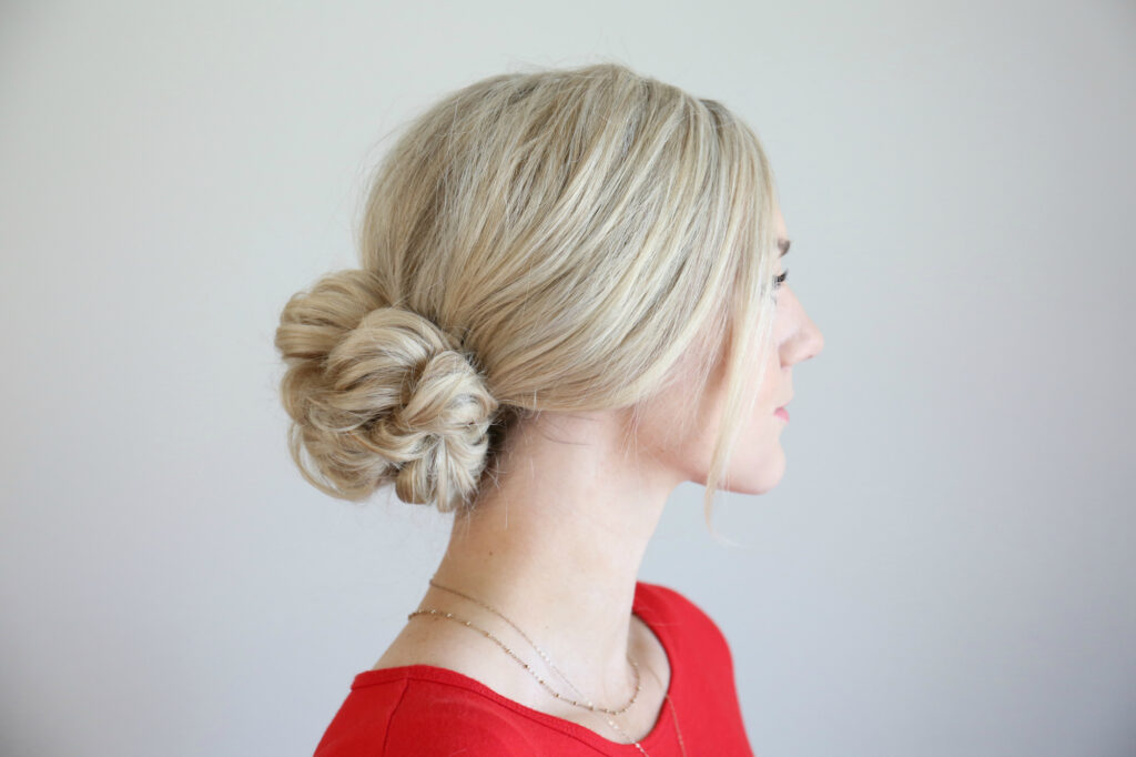"Profile of woman standing in front of a white background modeling the ""Pull Thru updo"" hairstyle"