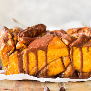 This Pumpkin Pull Apart Bread is full of warm pumpkin spice, sweet brown sugar and drizzled with a chocolate ganache!