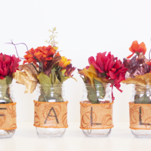Fall flowers place inside mason jars wrapped with fall themed ribbon