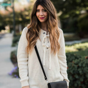 Woman outside wearing a white sweater, denim pants, and black crossbody bag