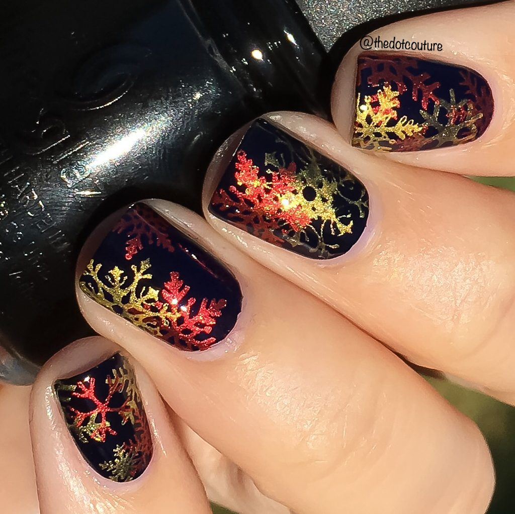 Black holiday nails with red and gold snowflakes nail art