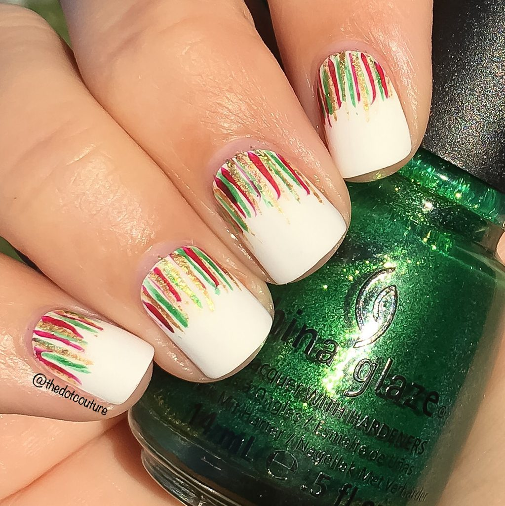 Holiday white painted nails with red, green, and gold streaks