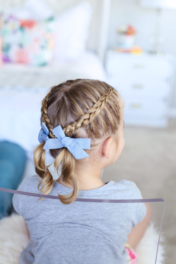 "Back view of little girl sitting in her room modeling ""Criss Cross Pigtails"" hairstyle"