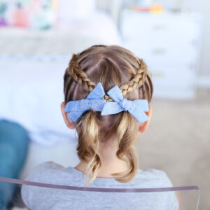 """Back view of little girl sitting in her room modeling """"Criss Cross Pigtails"""" hairstyle"""