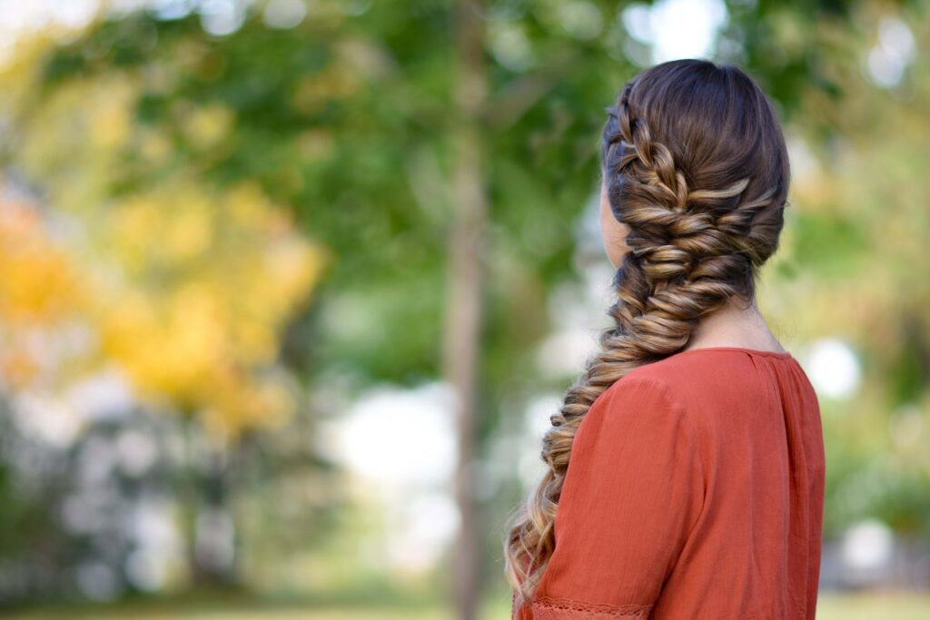 """Side view of girl outside wearing an orange shirt modeling """"Side Elastic Braid"""" hairstyle"""
