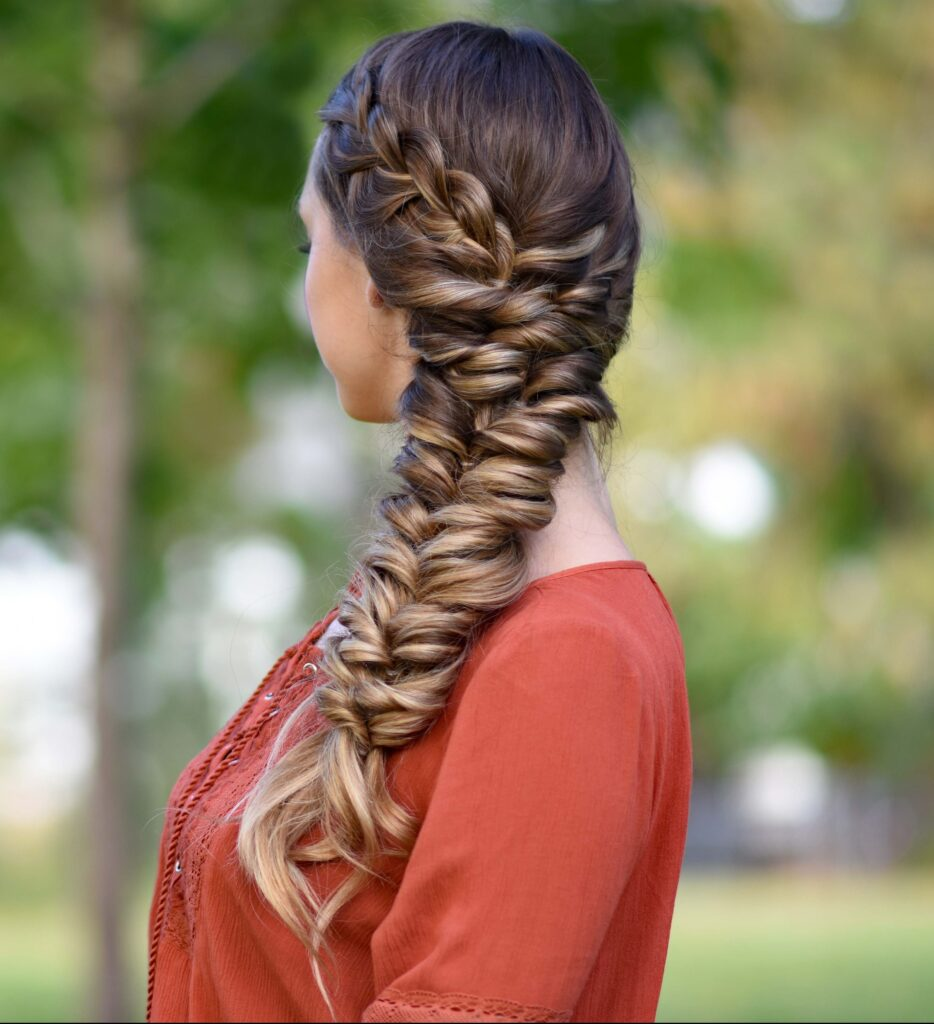 """Side view of girl standing outside wearing an orange shirt modeling """"Side Elastic Braid"""" hairstyle"""