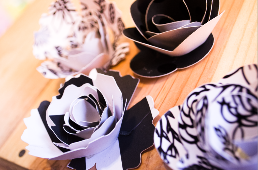 Black and white paper flowers place on top of a wooden table