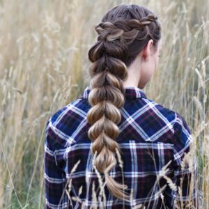 "Back view of young girl in the meadow wearing blue plaid shirt modeling ""Wrapped Pull-Thru Braid"" hairstyle"