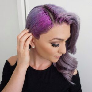 Side view of a young woman wearing a black shirt touching her purple hair and purple glitter gel