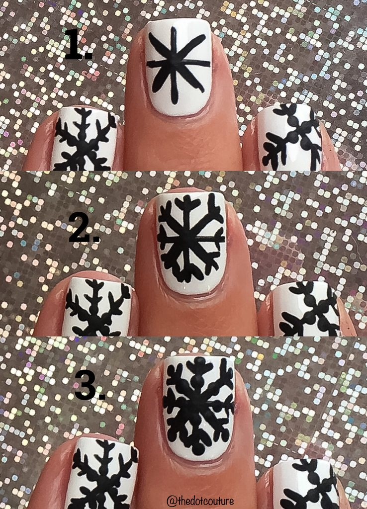 White painted nails with black snowflakes in front of glitter background