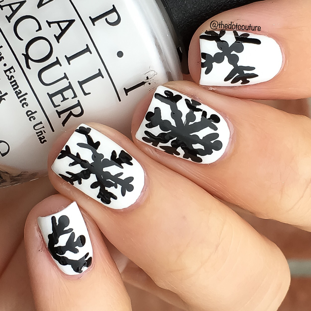 White painted nails with black snowflakes holding a white nail polish bottle