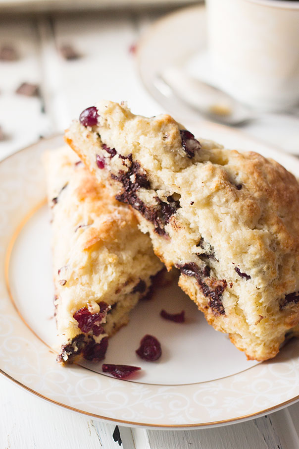 Two cherry and chocolate scones stacked and placed on a white plate