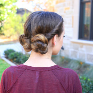 "Side view of girl with burgundy shirt outside modeling ""Twist Back Buns"" hairstyle"