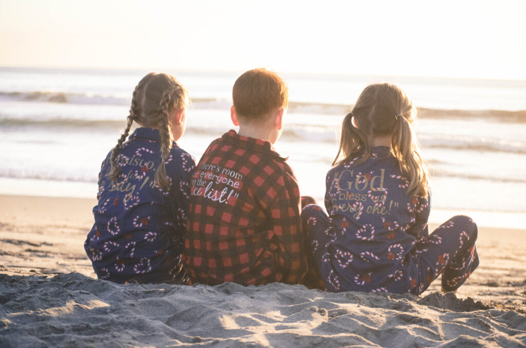 Two girls and one boy in the middle sitting on the beach in personalized Christmas pajamas