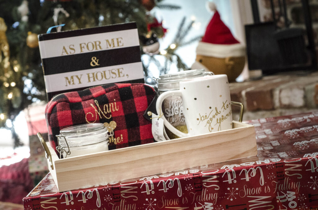 A notebook, makeup bag, coffee mug, and sugar place in a serving tray by the Christmas tree