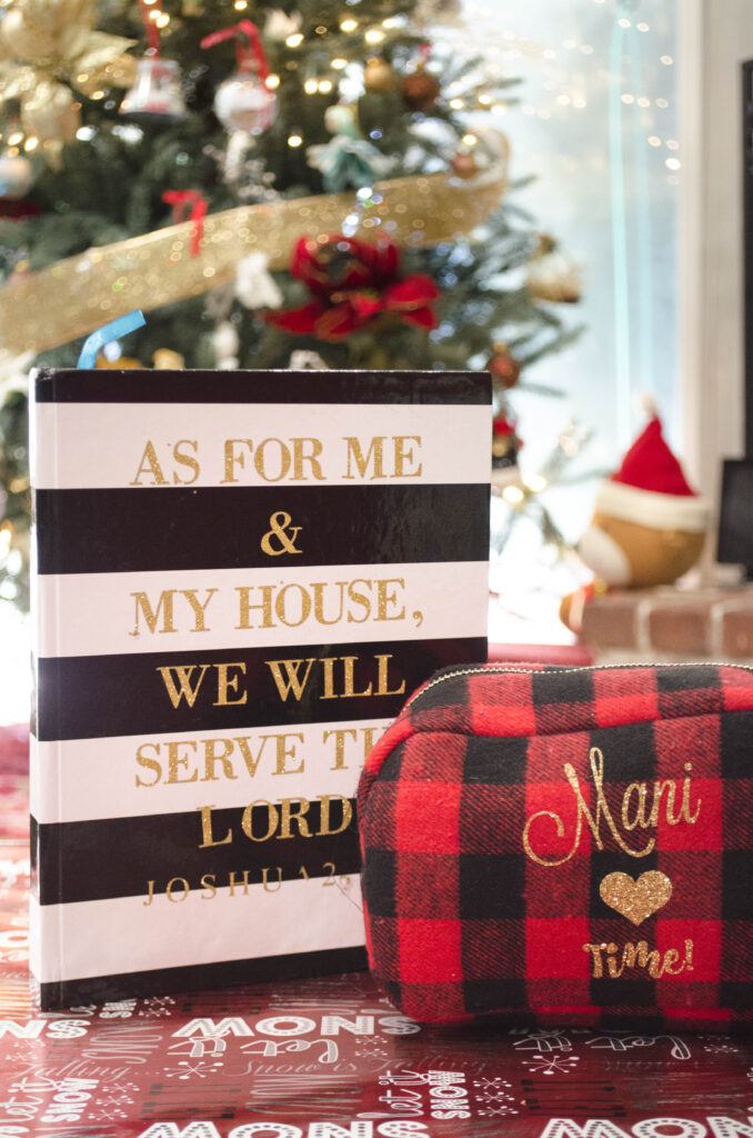 A black and white journal next to a red plaid makeup back placed close to a Christmas tree